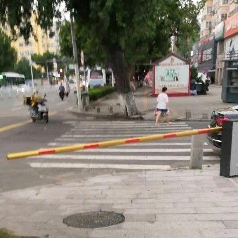停车杆拦住人行道。大客车跨双黄线逆行加塞