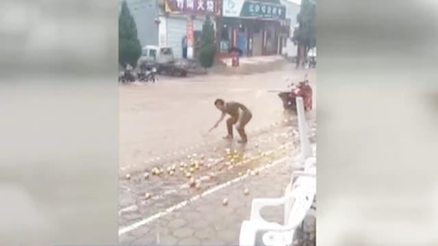 """暖心""""水果捞"""" 暴雨天男子用漏勺帮老板打捞苹果"""