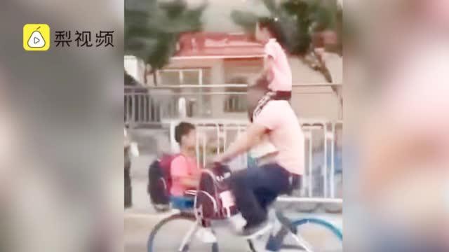 危险!父亲耍杂技式骑单车载俩娃,车筐坐一个肩膀骑一个