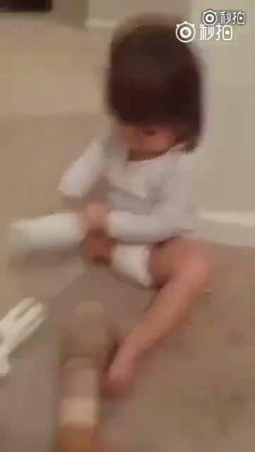 一个小女孩在妈妈的鼓励下,乖乖把义肢戴上……