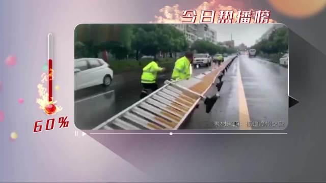 这一幕让人心疼!台风天执勤交警扶护栏被压倒