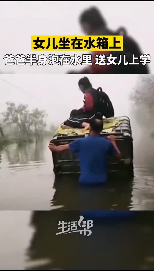 水库泄洪道路受阻,爸爸用水箱推行送女儿上学