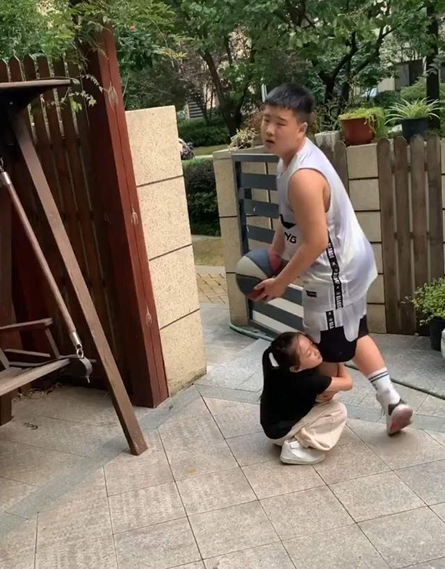 哥哥要去打篮球,妹妹强行抱哥哥大腿阻止,哥哥无奈模样笑翻妈妈
