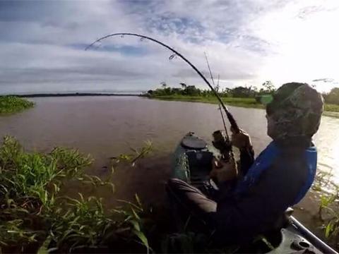 钓鱼男子没腾出手划船,船儿却快速的前进,水下的鱼扯线真大力