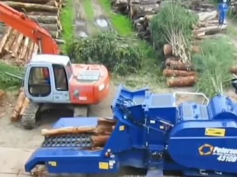 挖掘机机械手将木头放入移动式粉碎机中粉碎