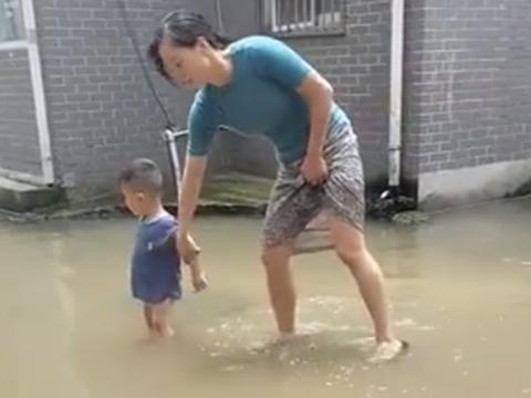 萌娃站在水坑里不知所措,亲妈单手拎娃引争议,网友:不怕脱臼?