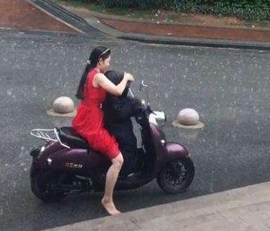 红衣女子冒大雨骑车,镜头转到孩子身上后,众人竖起大拇指点赞