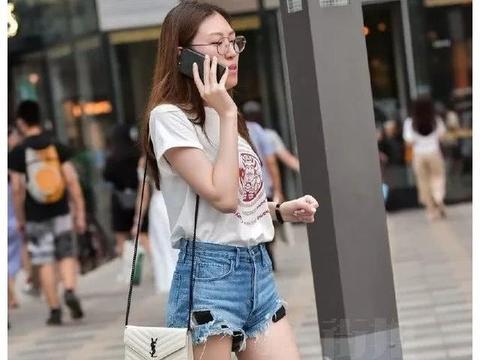 街拍美女:T恤热裤的小姐姐,带着一副金丝眼镜,看上去很知性
