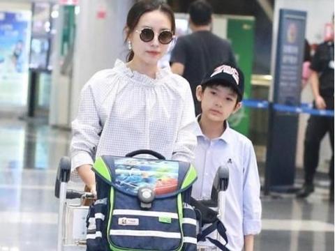 40岁董洁推行李带儿子现身机场,穿长裙好时尚,儿子太像妈妈了