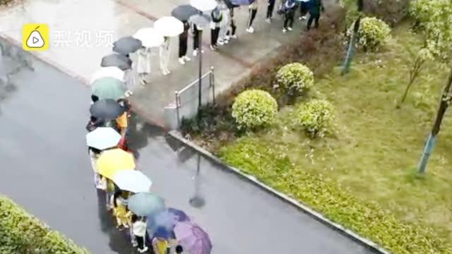 近60名师生雨中搭百米伞桥