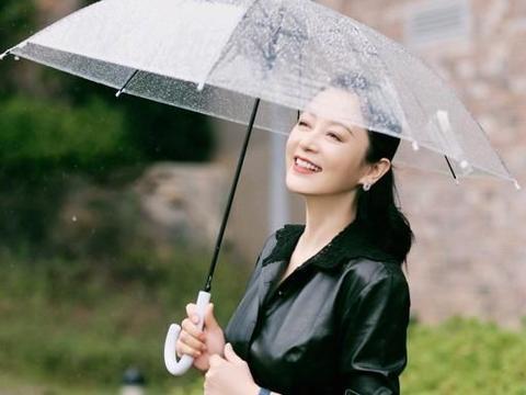 51岁陈红回乡雨中漫步,矅黑色钩花皮衣腰肢纤细,配百褶裙真优雅