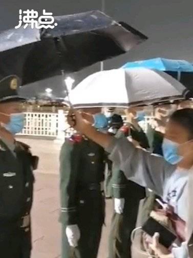 市民为天安门前雨中执勤哨兵撑伞