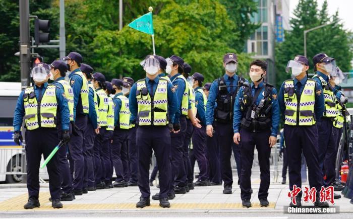 """资料图:10月3日,韩国多个民间团体发起""""免下车""""集会,首尔调动大批警力严防疫情。图为大批警察在首尔光化门广场附近,严防人员聚集。 中新社记者 曾鼐 摄"""