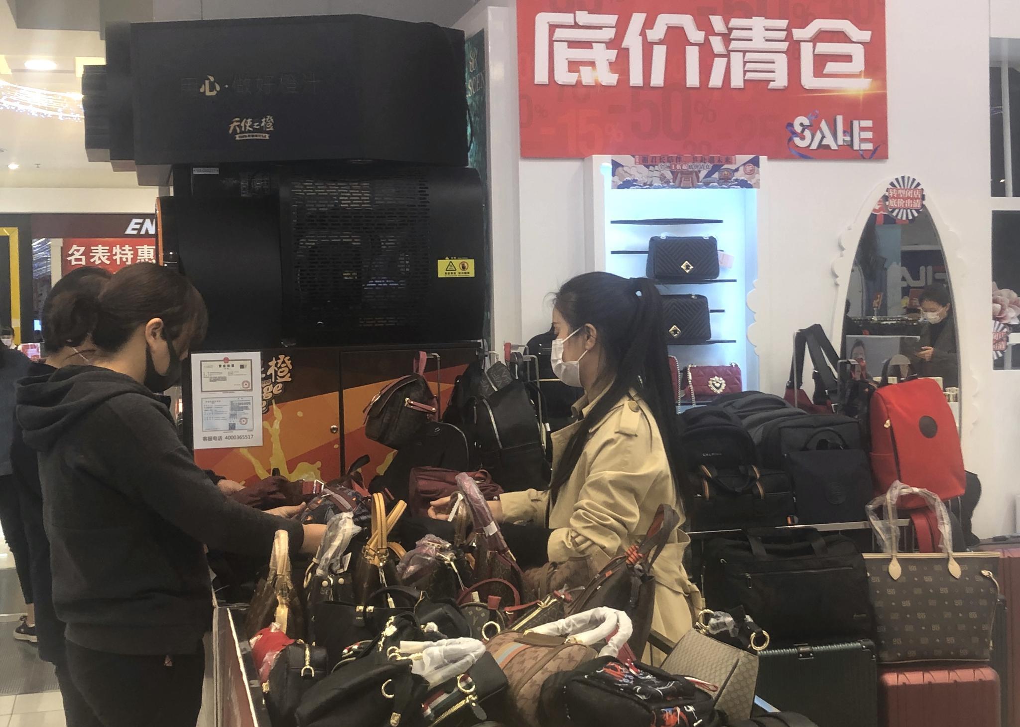 东安市场,一位主顾正在皮包柜台挑选商品。拍照/新京报记者 吴宁