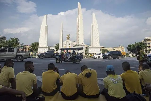 """本地时候10月14日,泰国曼谷再次发作反当局请愿聚会,以青年门生为主的请愿者群集在曼谷民主怀念碑四周,并与一部门支撑当局、附和王室的""""保皇派""""猛烈僵持,乃至产生了小范围肢体辩论。图源:人民视觉"""