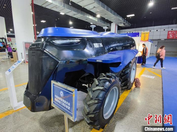 """图为""""一带一路""""(洛阳)国际农业合作博览会上,展出的多用途智能新能源轮式拖拉机,可进行耕、耙、播、收等作业。 阚力 摄"""