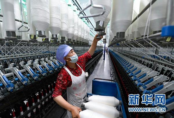在宁夏吴忠市红寺堡区现代纺织产业园内,移民在生产线上忙碌(6月7日摄)。新华社记者 冯开华 摄
