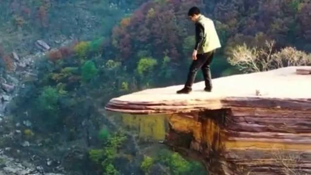 这小伙子胆子真大,敢在那么危险的地方看山崖下边……