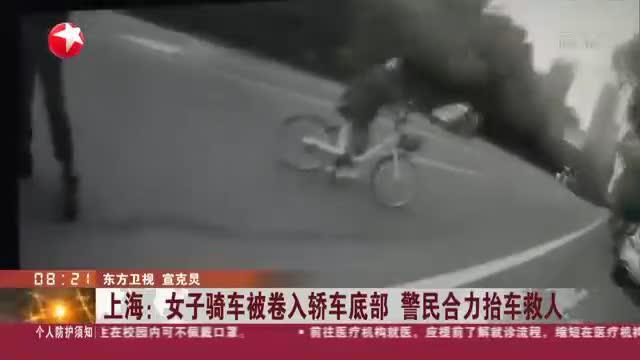 上海:女子骑车被卷入轿车底部  警民合力抬车救人
