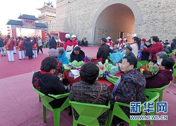重阳寿辰庆典仪式上,99位老人围桌而坐吃蛋糕、看节目。