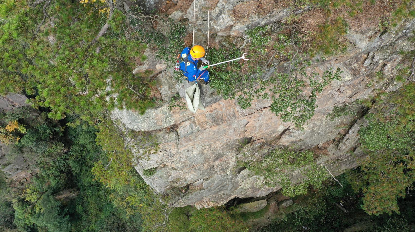 蓝天救援队成员悬崖绝壁上捡拾垃圾:扔起来简单捡起来难