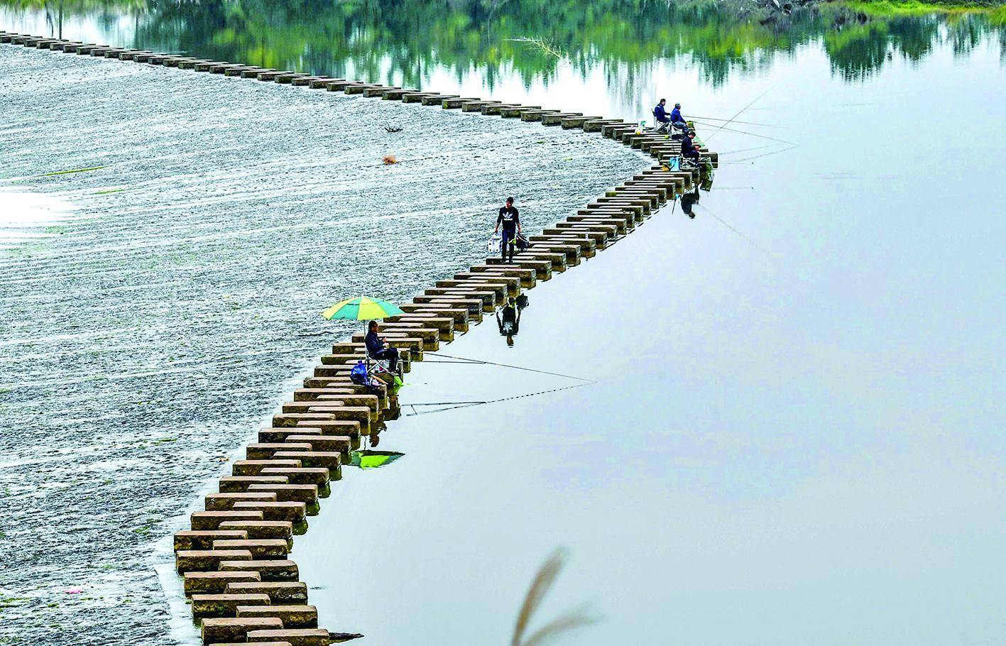 垂钓爱好者坐在永安溪水碇步上尽情地享受着垂钓的乐趣