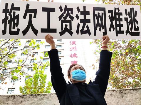 """山东滨州一女子街头高举""""拖欠工资法网难逃"""""""