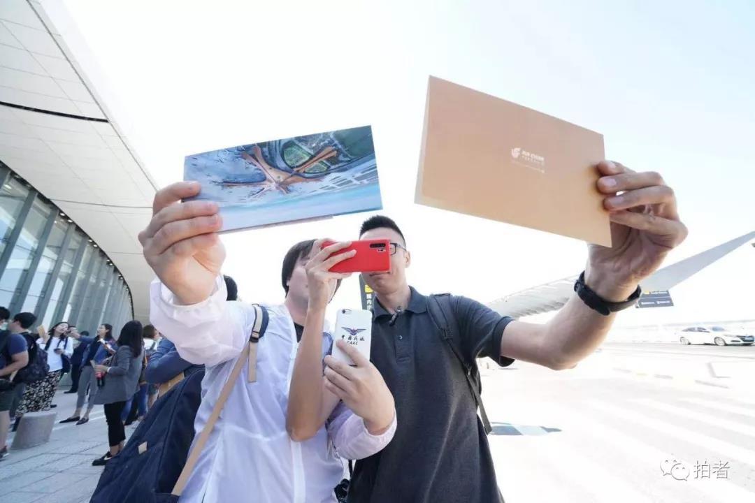 △ 2019年9月25日,加入初次通航运动的游客拿着乘机约请函自拍留念。拍照/新京报记者陶冉