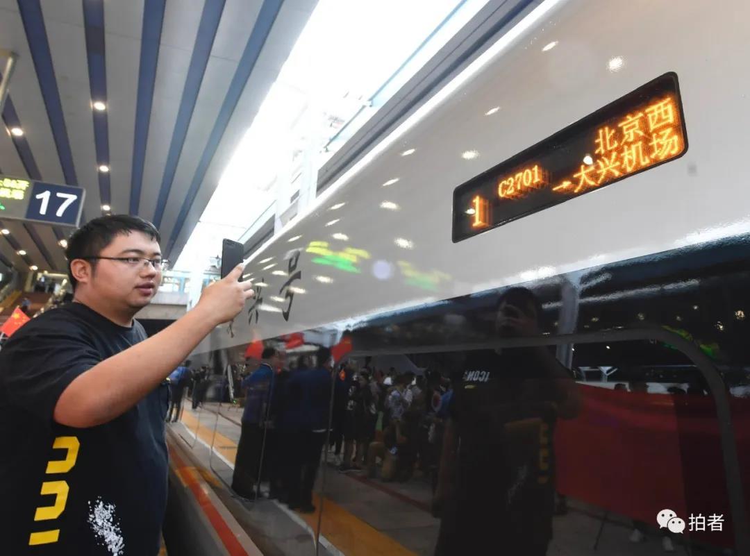 △ 2019年9月26日6时49分, 搭客在拍摄由北京西站开往大兴机场的首发列车C2701次。当天,京雄城际铁路(北京段)正式开通。拍照/新京报记者吴宁