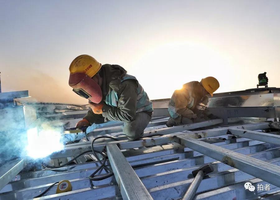 △ 2018年1月16日,施工职员正在航站楼楼顶举行焊接功课。拍照 /新京报记者王飞