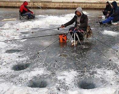 男子拿着七根钓鱼竿,在冰上打洞钓鱼,路人担心男子的安全