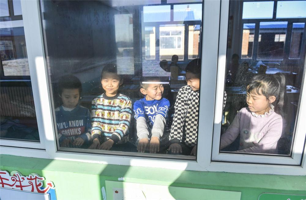 吉林省德惠市边岗乡卧虎村小学学生在户外活动后围着教室内的环流散热器取暖(2018年12月26日摄)。新华社记者 许畅 摄
