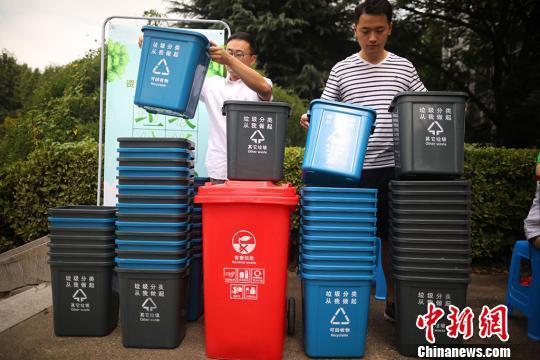 """资料图:大门生将印有""""垃圾分类,从我做起""""字样的垃圾桶摆放整洁。泱波 摄"""