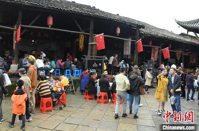四川犍为:游客参观古镇看表演 食物是生