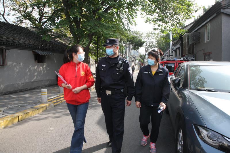 金宝街北社区民警白艳滨与同事在胡同里走访。新京报记者 王飞 摄
