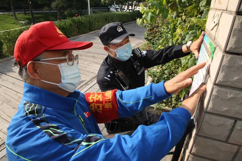 刘士琦和社区自愿者一路张贴防诈骗及平安常识宣传海报。新京报记者 王飞 摄
