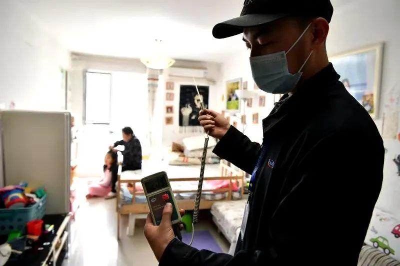 测温员在居民家中测温,仪器显示室温20.9℃。摄影吴江