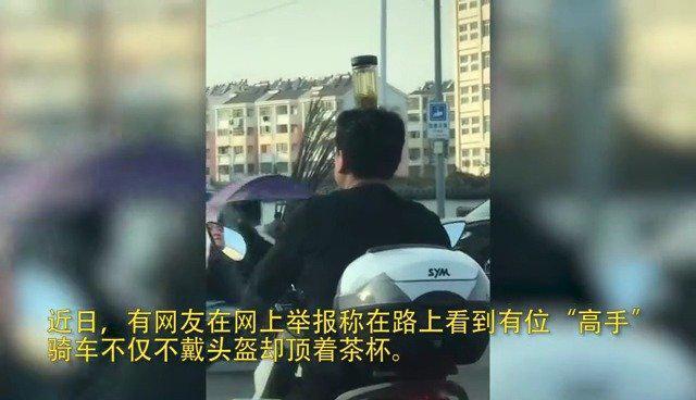 骑摩托不戴头盔顶茶杯 交通安全不容儿戏!
