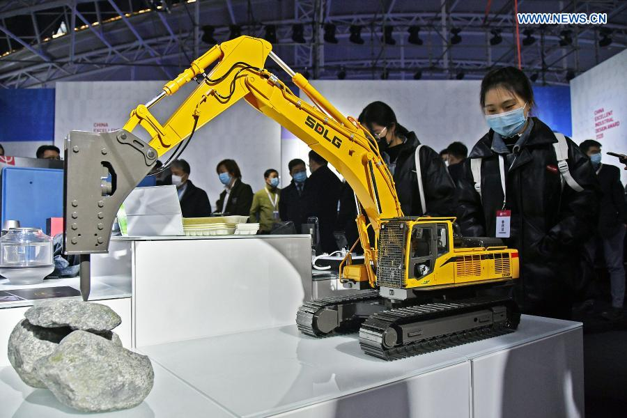 A visitor views an excavator model during the 2020 World Industrial Design Conference in Yantai, east China's Shandong Province, Nov. 25, 2020. The 2020 World Industrial Design Conference is held from Nov. 25 to 29 in Yantai. The conference also includes an exposition of China's top industrial designs, with over 800 domestic companies showcasing over 1,000 exhibits of new technology, new design and new products. (Photo by Sun Wentan/Xinhua)