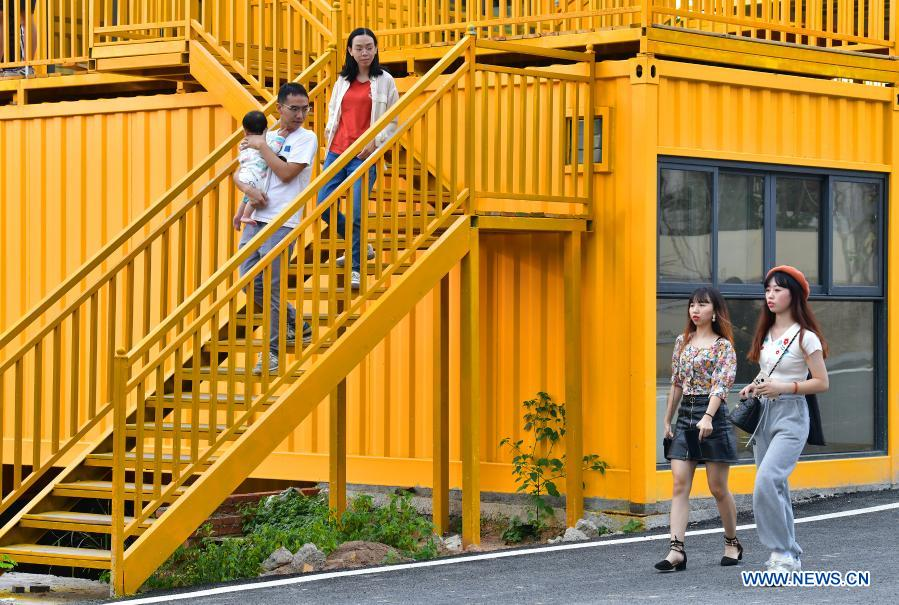 Young tourists are seen at colorful houses built with repurposed shipping containers in Beilian Village, Xiyang Township of Meizhou City in south China's Guangdong Province, Nov. 21, 2020. In recent years, Meizhou, hometown to many overseas Chinese, has stepped up with its efforts preserving ecological environment and improving living environment in the rural areas to boost village tourism. (Xinhua/Li He)