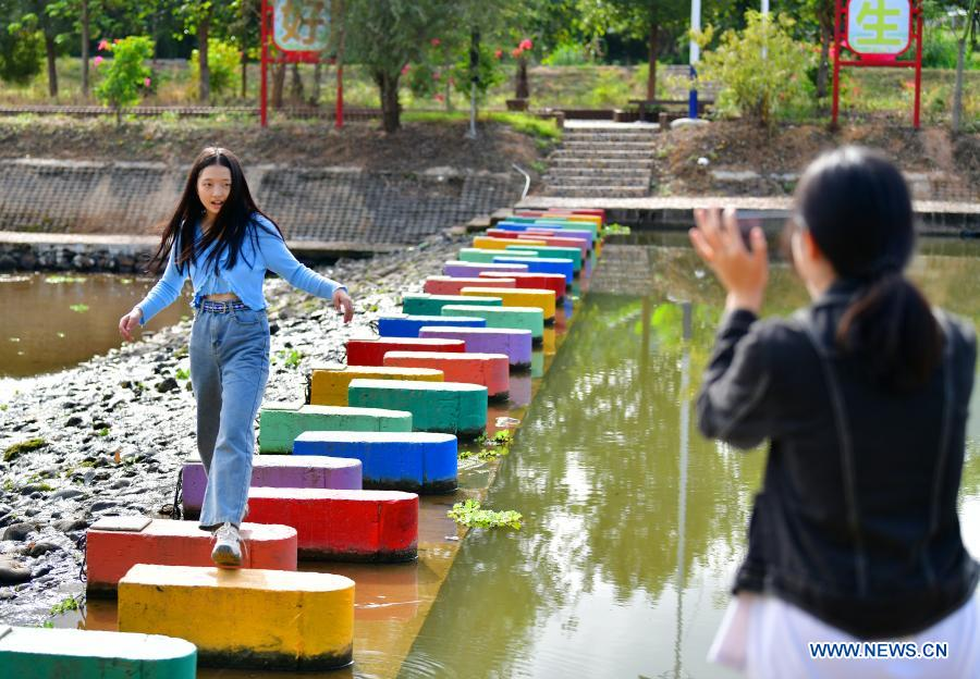A tourist poses for photos at a recently renovated dam in Zhikeng Village, Xiyang Township of Meizhou City in south China's Guangdong Province, Nov. 21, 2020. In recent years, Meizhou, hometown to many overseas Chinese, has stepped up with its efforts preserving ecological environment and improving living environment in the rural areas to boost village tourism. (Xinhua/Li He)