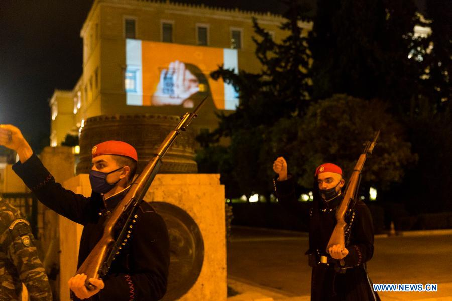 Members of the Presidential Guard walk past the Greek Parliament building on which a projection saying