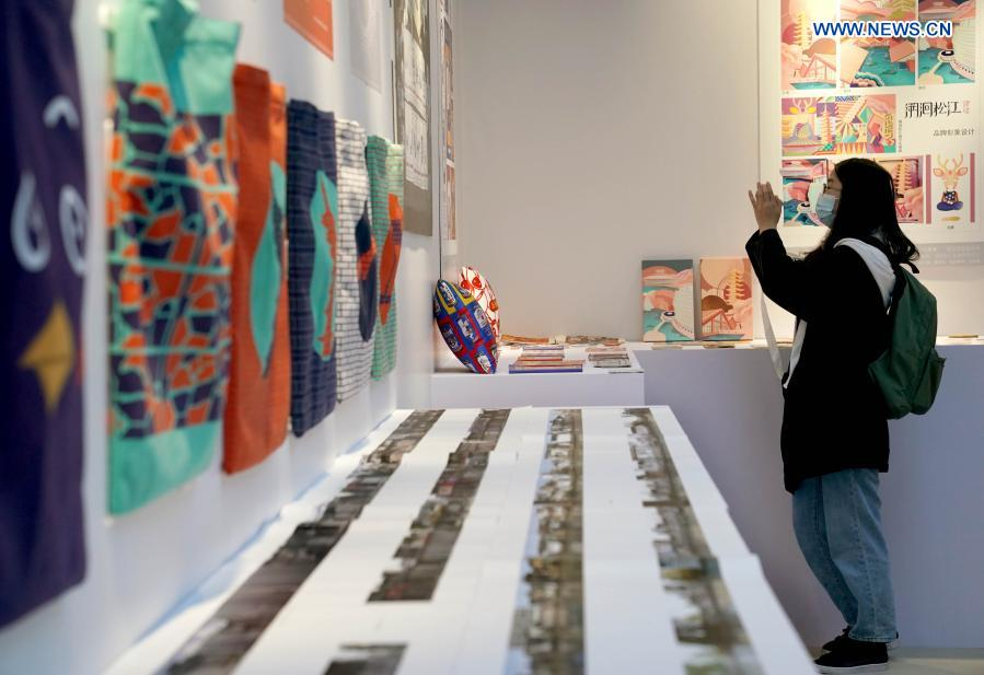 A visitor enjoys artworks of visual communication design during the 5th