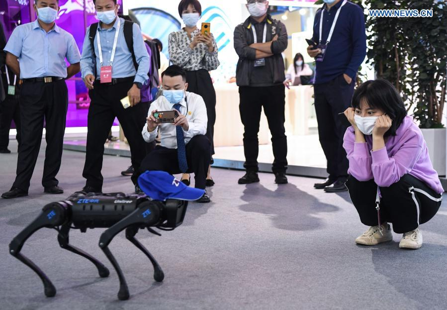 Visitors watch a robotic dog at a 5G-themed exhibition held during the World 5G Convention in Guangzhou, south China's Guangdong Province, Nov. 26, 2020. The 2020 World 5G Convention kicked off in Guangzhou Thursday, during which world-renowned infocom scientists, 5G service providers and 5G application adopters will exchange ideas on aspects of cutting-edge technologies, industrial development trends and innovative applications in 5G industry. (Xinhua/Deng Hua)