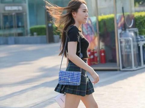 黑色的半袖T恤搭配蓝色的格子图案的百褶短裙,简单而时尚的美感