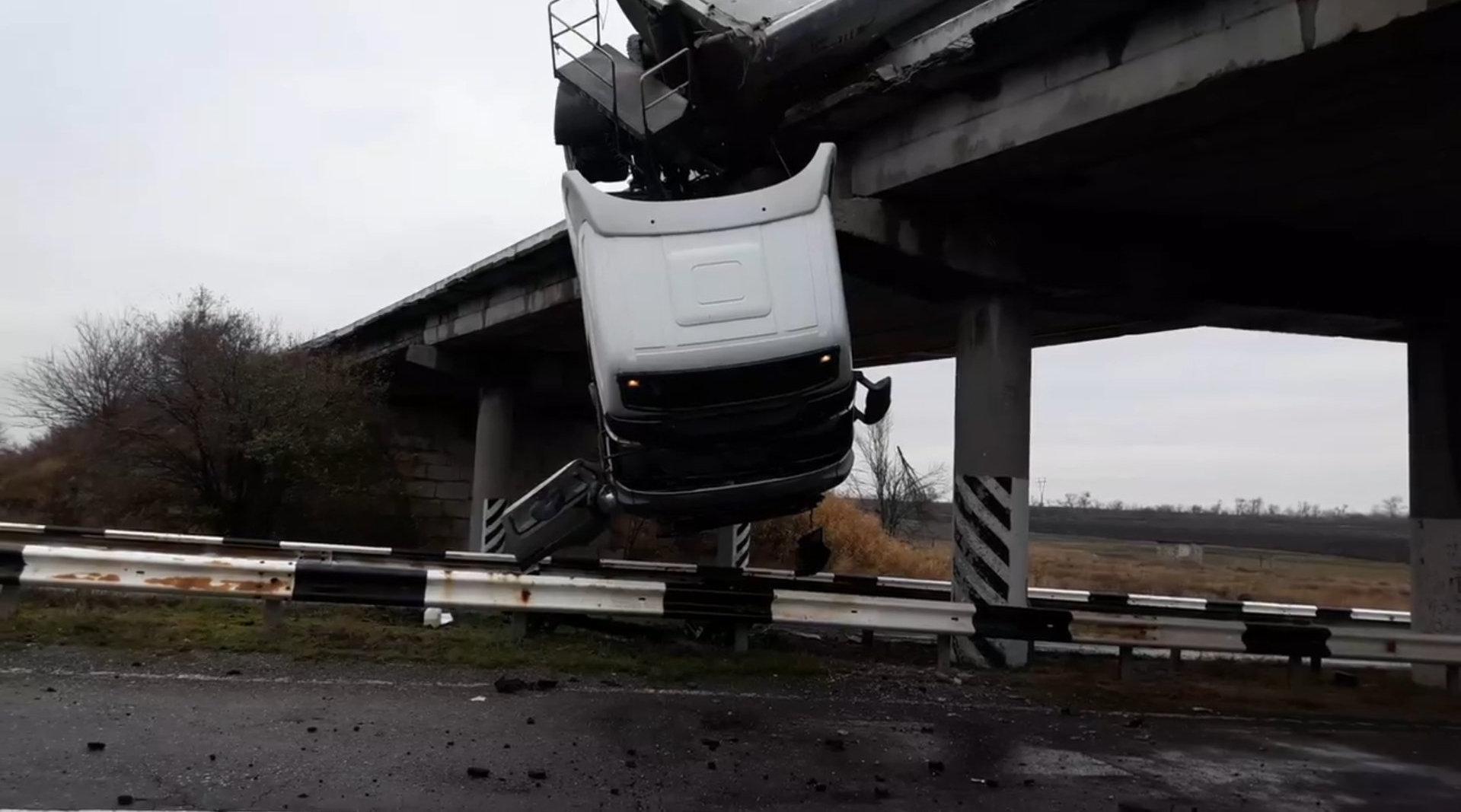 乌克兰一卡车冲破护栏 倒挂在桥上