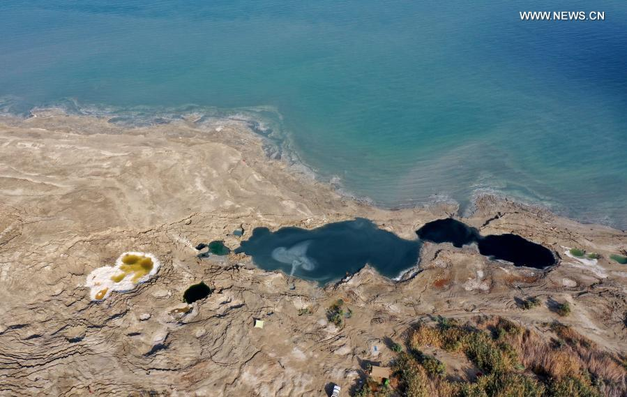 Sinkholes are seen on the shore of the Dead Sea near Ein Gedi beach on Nov. 28, 2020. As the Dead Sea is shrinking and its water levels decreasing, hundreds of sinkholes are devouring land where the shoreline once stood. (Photo by Gil Cohen Magen/Xinhua)