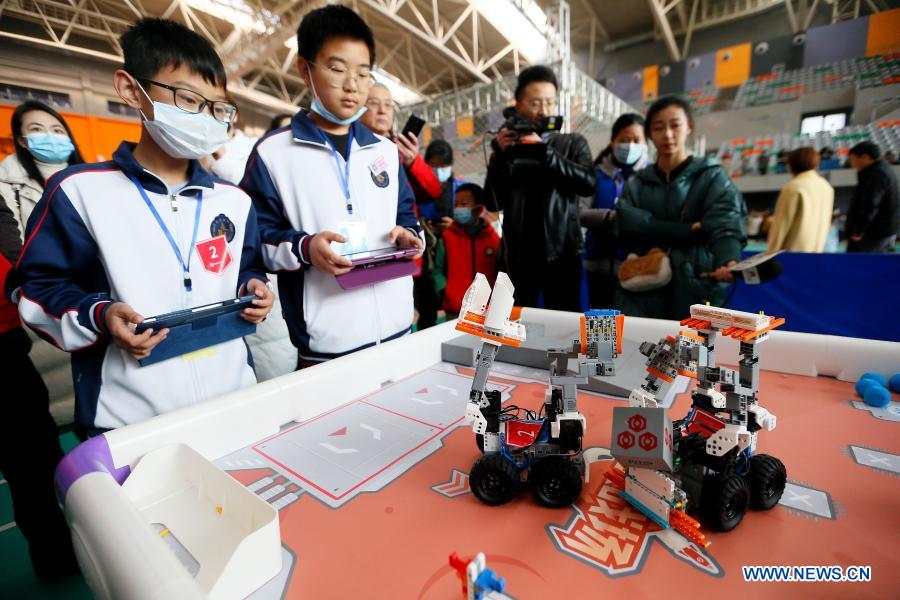 Contestants participate in a robot rescue match during a robotics competition for middle and primary school students in Jimo District of Qingdao, east China's Shandong Province, Nov. 29, 2020. The robotics competition has 20 categories, attracting more than 300 middle and primary student contestants from across Jimo District. (Photo by Liang Xiaopeng/Xinhua)