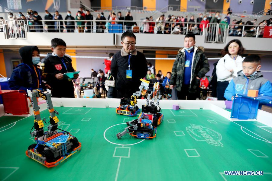 Contestants participate in a robot soccer match during a robotics competition for middle and primary school students in Jimo District of Qingdao, east China's Shandong Province, Nov. 29, 2020. The robotics competition has 20 categories, attracting more than 300 middle and primary student contestants from across Jimo District. (Photo by Liang Xiaopeng/Xinhua)