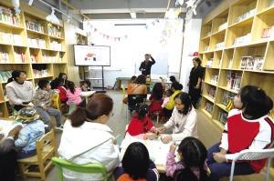"""父母和孩子在""""惠民书市""""静心阅读"""